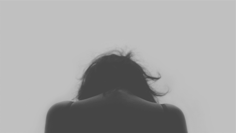Canva - Moody image of woman looking down